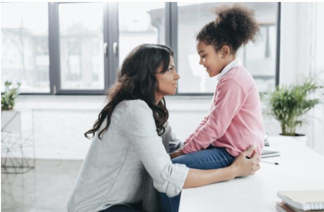 Woman talking to child about mental health wellness.