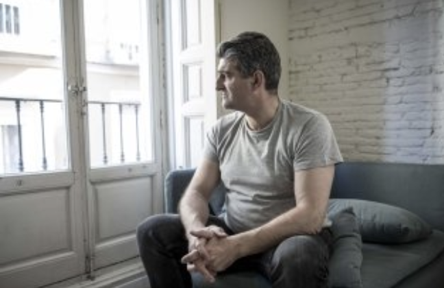 Man with anxiety looking out sunny window.